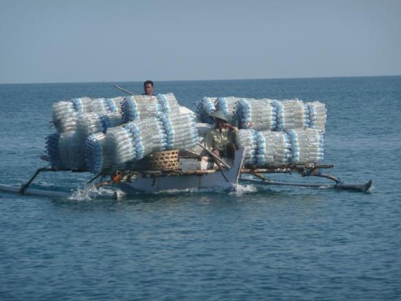 Medana bay – Lombok. Pirogue de pêche reconvertie en transport de bouteilles d'eau pour les touristes des Gili.