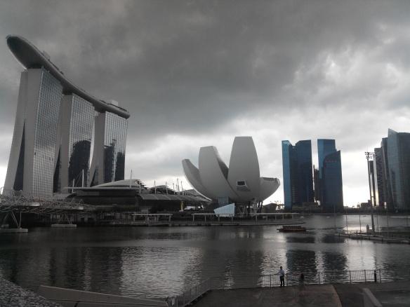 Singapour – Marina Bay Sands et Lotus musée des sciences. Le Marina Bay Sands est un hôtel de 2560 chambres. Il abrite un casino et une piscine à débordement posée sur le dernier étage, le tout sis à côté d'un immense centre commercial où se côtoient les enseignes de luxe. Il est le symbole de la démesure de Singapour mais a pour fonction d'accroître la durée moyenne de séjour touristique sur l'ile,de 2.5 à 3 jours…