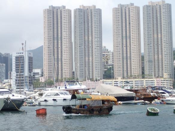 Hong Kong – Sampan en maraude dans le port d'Aberdeen situé au sud de l'ile dans un trou à cyclone. Le village flottant de jonques et de sampans, incendié le 25 décembre 1986 – 150 sampans coulés –, bordel traditionnel de la ville a été remplacé par une marina et les immeubles d'habitation ont grignoté la jungle. Quelques sampans continuent à faire taxi.