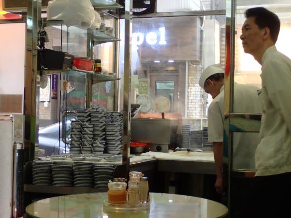 """Hong Kong – Mac's noodles à Wellington street. Mac's est célèbre pour sa """"Wanton noodle soup"""", soupe de ravioli servie en petites portions et pour ses serveurs en livrée. Le bouillon non bu est reversé dans la marmite. Les amateurs dégustent leur soupe plutôt en fin d'après-midi, les bouillons reversés ont eu le temps de se faire culture."""
