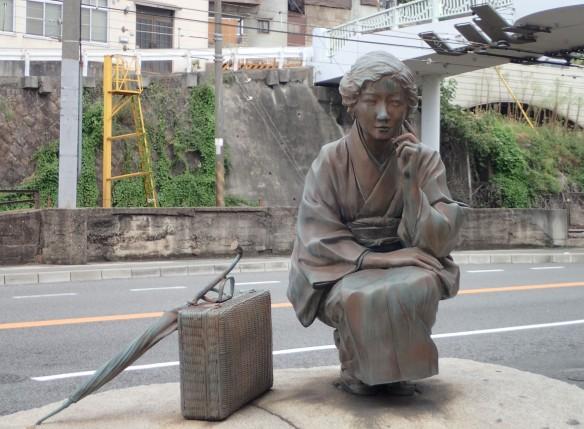 Sculpture à l'entrée du Shotengai d'Onomichi. Shotengai : galeries de magasins du centre-ville présentes dans la majorité des villes japonaises aujourd'hui remarquables par leurs produits « vintage » et qui connaissent un déclin certain.