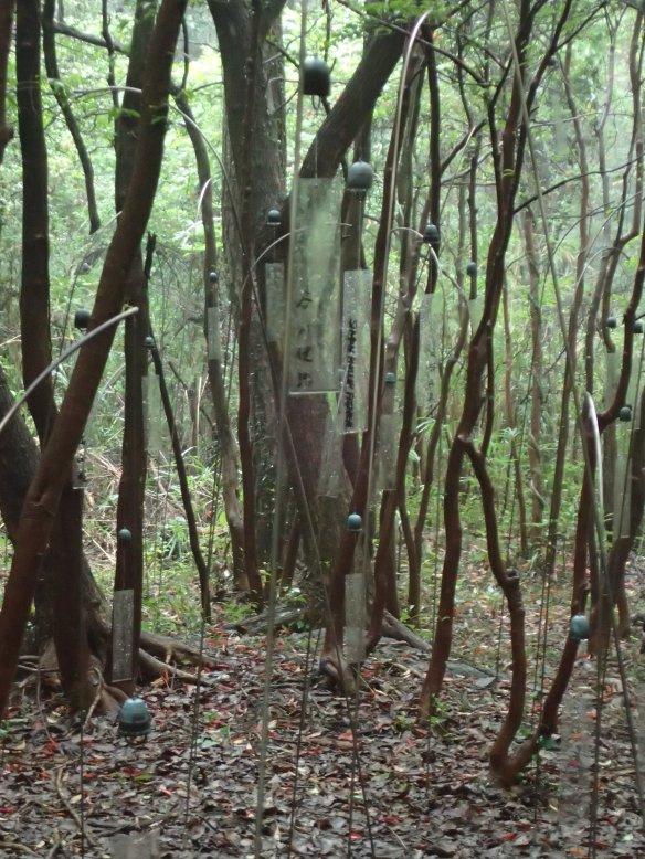 La forêt des murmures – Christian Boltanski - Teshima Au fin fond de la forêt, une plaque transparente qui porte le nom d'une personne décédée est accrochée sous chaque grelot. Dans une pure tradition bouddhiste, le vent rend ainsi hommage à l'âme du défunt.
